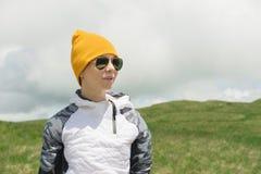 Porträt eines attraktiven Mädchens in der Sonnenbrille und in einem Hut auf dem Hintergrund von tiefen Wolken und von grünen Hüge lizenzfreies stockbild