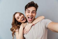Porträt eines aufgeregten jungen Paarumarmens Stockfotografie