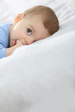 Porträt eines Babys, das auf Bett liegt Stockbild