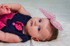 Porträt eines Babys in einem Kleid mit Windeln mit einem Bogen auf ihrem Kopf, der auf dem Bett in ihrem Raum liegt Stockbild