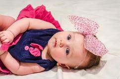 Porträt eines Babys in einem Kleid mit Windeln mit einem Bogen auf ihrem Kopf, der auf dem Bett in ihrem Raum liegt Lizenzfreies Stockbild