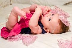 Porträt eines Babys in einem Kleid mit Windeln mit einem Bogen auf ihrem Kopf, der auf dem Bett in ihrem Raum liegt Stockbilder