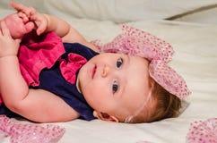 Porträt eines Babys in einem Kleid mit Windeln mit einem Bogen auf ihrem Kopf, der auf dem Bett in ihrem Raum liegt Lizenzfreie Stockfotos