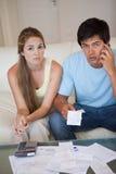Porträt eines besorgten Paares, das ihre Empfänge betrachtet Lizenzfreies Stockfoto