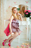 Porträt eines bezaubernden blonden Mädchens im rosa Kleid, sitzend am Th stockfotografie