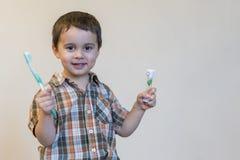 Porträt eines blonden Jungen des schönen netten Kaukasiers mit einer Zahnbürste Bürstende Zähne des kleinen Jungen und Lächeln be lizenzfreie stockbilder