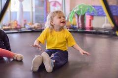Porträt eines blonden Jungen in einem gelben T-Shirt Das Kinderlächeln und -spiele im Spielzimmer der Kinder Das Kind springt auf lizenzfreies stockfoto