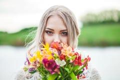 Porträt eines blonden Mädchens mit einem Blumenstrauß von Blumen Nahaufnahme stockfotografie