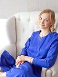 Porträt eines blonden Mädchens, welches das blaue Kleid sich entspannt auf dem Stuhl trägt lizenzfreie stockfotografie
