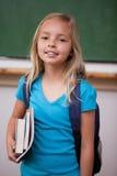 Porträt eines blonden Schulmädchens, das ihre Bücher hält lizenzfreie stockfotos