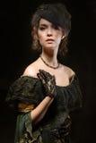 Porträt eines Brunette in einem Hut und in den Handschuhen Stockfotografie