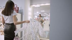 Porträt eines brunette Mädchens in einem Bekleidungsgeschäft in einem Mall wählt zwischen zwei Kleidern vor einem Spiegel stock video footage