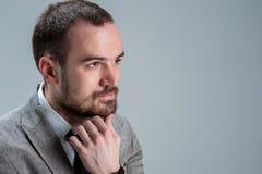 Porträt eines denkenden Mannes, der zur Seite schaut und Hand unterstützt Stockfotografie