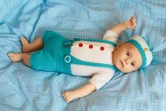 Porträt eines drei Monate alte Babys in einer blauen gestrickten Klage auf einer blauen Decke im Kindertagesstättenraum Flache La stockfotos
