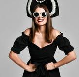 Porträt eines eleganten brunette schwarzen Kleides, der schwarzen Sonnenbrille, der kokoshnik Kappe, des langen Haares und des sc stockbild