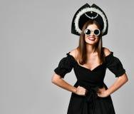 Porträt eines eleganten brunette schwarzen Kleides, der schwarzen Sonnenbrille, der kokoshnik Kappe, des langen Haares und des sc stockfotografie
