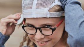 Porträt eines elfjährigen blonden Mädchens mit Gläsern und einer Kappe Stellen Sie Nahaufnahme gegenüber stock footage
