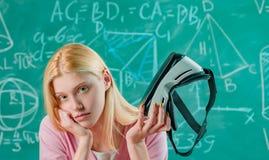 Porträt eines enttäuschten Blondinestudenten, der Kopfhörer der virtuellen Realität auf grünem Tafelhintergrund hält lizenzfreies stockbild