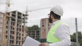 Porträt eines erfolgreichen jungen Ingenieurs oder des Architekten, die einen weißen Sturzhelm, schauend in den Bauzeichnungen in stock video footage