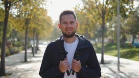 Porträt eines erfolgreichen jungen touristischen Mannstudentenoffiziers, Manager nach der Arbeit, ein öffentlicher Ort, Blicke in stock video footage