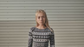 Porträt eines ernsten jugendlich Mädchens auf einem grauen gestreiften Hintergrund stock footage