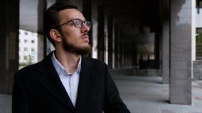 Porträt eines ernsten jungen Rechtsanwalts mit Gläsern und klassischer Klage Richtet den Kragen gerade und betrachtet die Kamera stock footage
