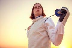Porträt eines Fechtermannes, der seine Klinge auf den Schultern auf einem sonnigen Hintergrund hält und vorwärts dreamingly schau Lizenzfreie Stockfotos