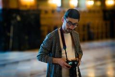 Porträt eines Fotografen des jungen Mannes mit den Gläsern, welche die Kamera, in der großen Halle betrachten Lizenzfreie Stockbilder