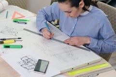 Porträt eines Frauenarchitekten bei der Arbeit über eine Gebäudeprojektplanung, auf dem Tisch Papier, Machthaber, Bleistifte, Kom Lizenzfreies Stockfoto