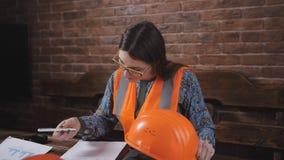 Porträt eines Fraueningenieurs an dem Arbeitsplatz Fraueningenieur im Sturzhelm und in der Schutzweste sitzt ha-Arbeit Schreibtis stock video footage