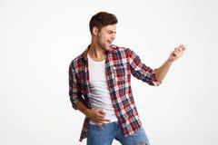 Porträt eines frohen jungen Mannes, der auf einer Gitarre spielt Lizenzfreie Stockbilder