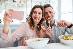 Porträt eines frohen jungen Paares, das ein selfie nimmt Lizenzfreie Stockbilder