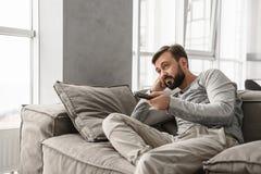 Porträt eines gebohrten jungen Mannes, der Fernsehen Fernsteuerungs hält Stockbild