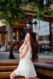 Porträt eines gelockten Mädchens mit einer Katze im Hintergrund stockfotografie