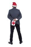 Porträt eines Geschäftsmannes, der einen Santa Claus-Hut mit holdin trägt Lizenzfreies Stockfoto