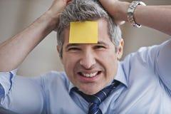 Porträt eines Geschäftsmannes mit klebender Anmerkung über Stirn Lizenzfreie Stockfotos