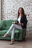 Porträt eines Geschäftstrainers der jungen Frau, der auf dem Sofaregal hält ein Notizbuch gerade schaut sitzt stockbild