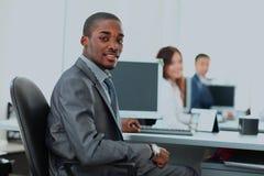 Porträt eines glücklichen Afroamerikanerunternehmers, der Computerlaptop im Büro anzeigt Lizenzfreies Stockfoto