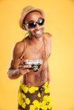 Porträt eines glücklichen afroen-amerikanisch Mannes, der Fotokamera hält Lizenzfreies Stockbild