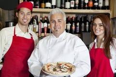 Porträt eines glücklichen Chefs, der Pizza mit Wartezeitpersonal hält Lizenzfreie Stockbilder