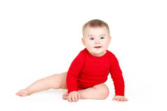 Porträt eines glücklichen entzückenden Säuglingskinderbaby-Lin-Rotes, welches das glückliche Lächeln auf einem weißen Hintergrund  Lizenzfreies Stockfoto