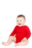 Porträt eines glücklichen entzückenden Säuglingskinderbaby-Lin-Rotes, welches das glückliche Lächeln auf einem weißen Hintergrund  Stockfoto