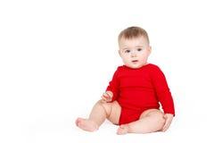 Porträt eines glücklichen entzückenden Säuglingskinderbaby-Lin-Rotes, welches das glückliche Lächeln auf einem weißen Hintergrund  Stockbilder