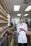 Porträt eines glücklichen Facharbeiters, der mit den Armen steht, kreuzte in der Werkstatt Stockbilder