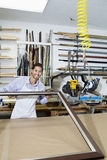 Porträt eines glücklichen Handwerkers, der am Bilderrahmen arbeitet Lizenzfreies Stockfoto