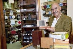 Porträt eines glücklichen Inhabers, der Zigarrenschachteln im Speicher zeigt stockfotos