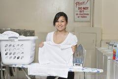 Porträt eines glücklichen jungen Angestellten, der im Waschautomaten bügelt Stockfoto