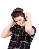Porträt eines glücklichen Jungen, der Musik auf Kopfhörern hört Stockfotos