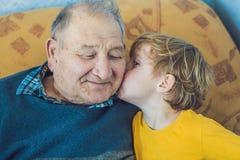 Porträt eines glücklichen Jungen, der glücklichen Opa küsst stockfoto