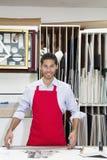 Porträt eines glücklichen jungen Facharbeiters, der mit Meterstock in der Werkstatt steht Stockfotografie